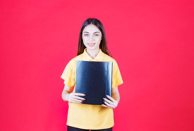 검은 폴더를 들고 노란색 셔츠에 젊은 여자