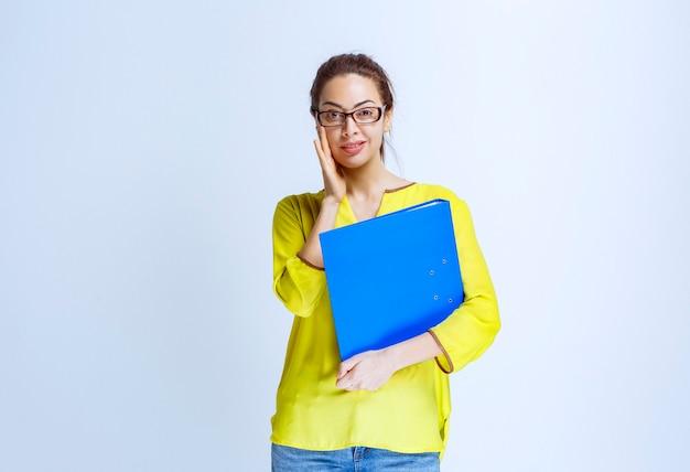파란색 폴더를 들고 노란색 셔츠를 입은 젊은 여성이 혼란스럽고 놀란 것처럼 보입니다.