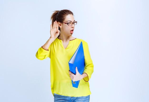 노란색 셔츠를 입은 젊은 여성이 파란색 폴더를 들고 혼란스럽고 놀란 것처럼 보입니다.