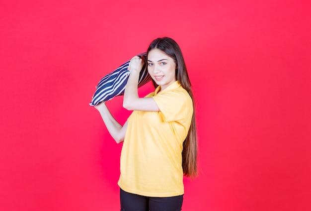 흰색 줄무늬가 있는 파란색 베개를 들고 베개 싸움을 하는 노란색 셔츠를 입은 젊은 여성