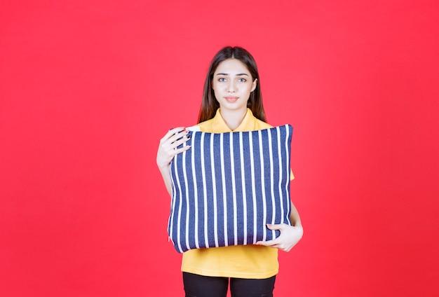 흰색 줄무늬가 있는 파란색 베개를 들고 노란색 셔츠를 입은 젊은 여성