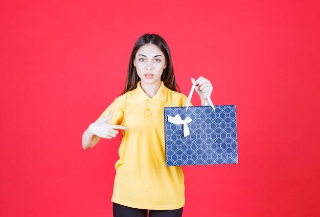 Молодая женщина в желтой рубашке держит синюю сумку для покупок
