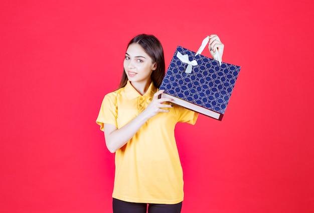 青い買い物袋を保持している黄色いシャツの若い女性