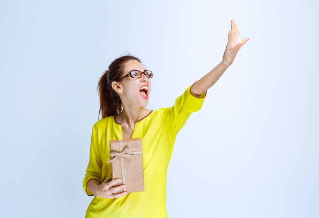 段ボールのギフトボックスを保持し、それを提示する人を招待する黄色いシャツの若い女性
