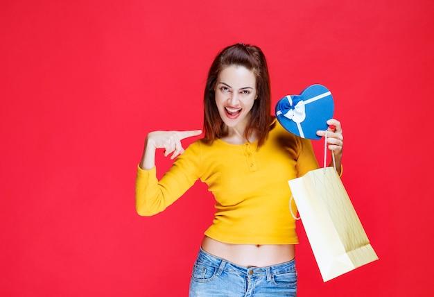 Молодая женщина в желтой рубашке держит картонную сумку для покупок, берет синюю подарочную коробку и чувствует себя удивленной