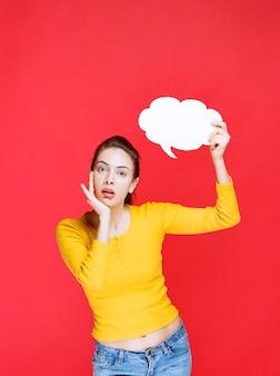 노란색 셔츠를 입은 젊은 여성이 구름 모양 정보 보드를 들고 불확실하고 사려깊게 보입니다.