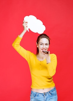 노란색 셔츠를 입은 젊은 여성이 구름 모양 정보 보드를 들고 음성 메시지를 보냅니다.