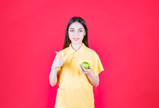 녹색 사과를 들고 만족감을 느끼는 노란색 셔츠를 입은 젊은 여성