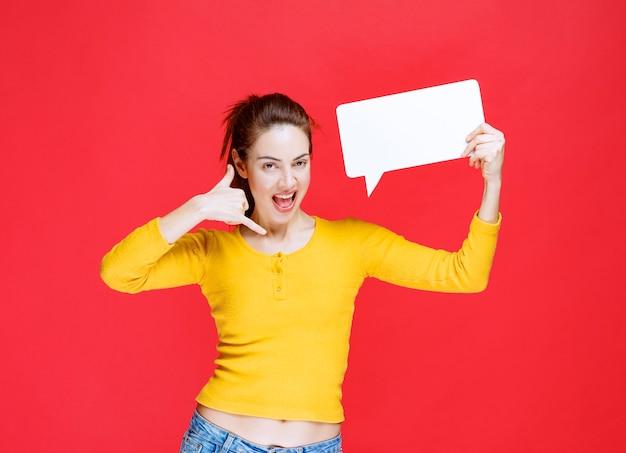 직사각형 정보 게시판을 들고 추가 질문이 있는 전화를 요청하는 노란색 셔츠를 입은 젊은 여성