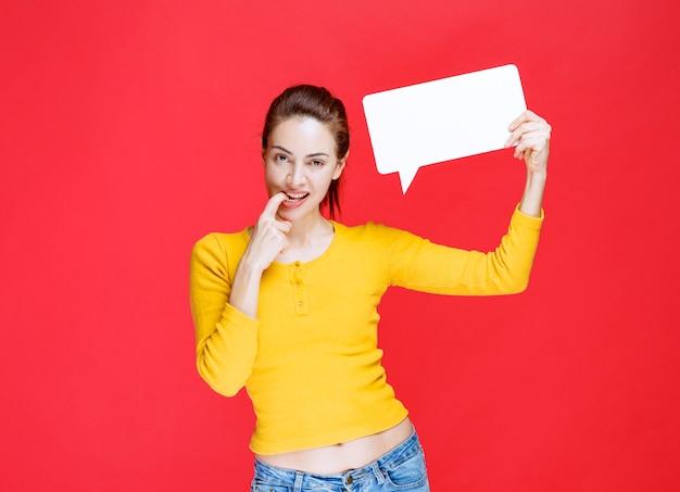 노란색 셔츠를 입은 젊은 여성이 직사각형 정보 보드를 들고 혼란스럽고 확신이 없어 보입니다.