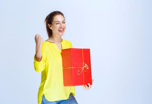 Молодая женщина в желтой рубашке держит красную подарочную коробку и показывает знак рукой удовольствия