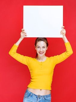 Молодая женщина в желтой рубашке держит квадратное информационное табло
