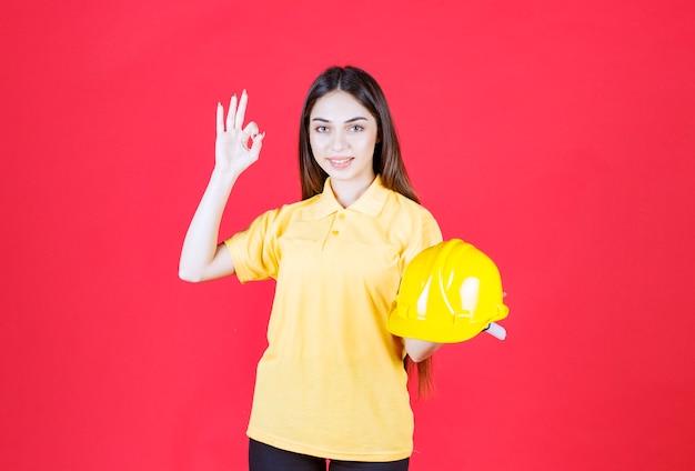 노란색 헬멧을 들고 제품을 즐기는 노란색 셔츠를 입은 젊은 여성