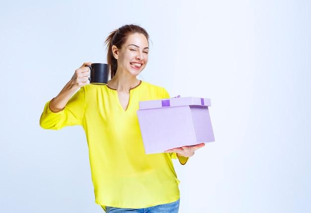 Молодая женщина в желтой рубашке держит открытую подарочную коробку за чашкой кофе
