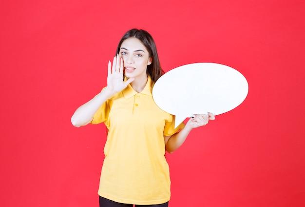 타원형 정보 보드를 들고 모든 사람에게 프로젝트에 대해 알리는 노란색 셔츠를 입은 젊은 여성
