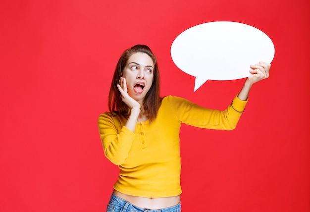 Молодая женщина в желтой рубашке держит овальную информационную доску и выглядит смущенной и задумчивой