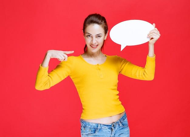 타원형 정보 보드를 들고 노란색 셔츠에 젊은 여자