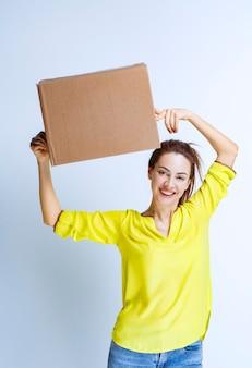 Молодая женщина в желтой рубашке держит картонную грузовую коробку и чувствует себя счастливой