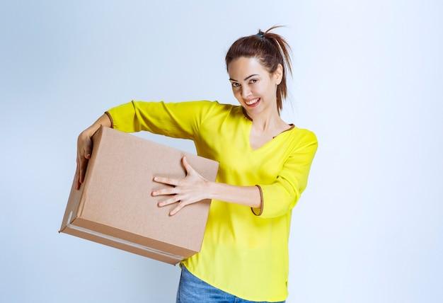 노란색 셔츠를 입은 젊은 여성이 판지 화물 상자를 들고 행복감을 느끼고 있습니다.