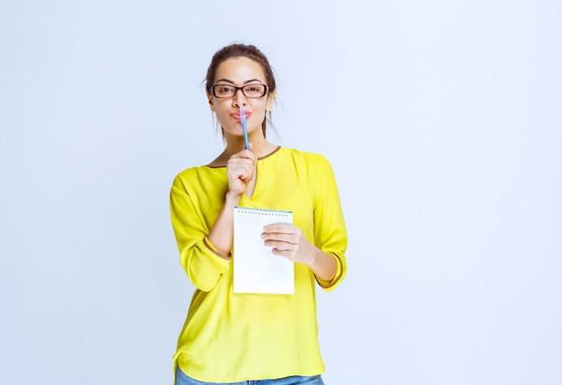 시험지를 들고 펜을 들고 생각하는 노란색 셔츠를 입은 젊은 여성