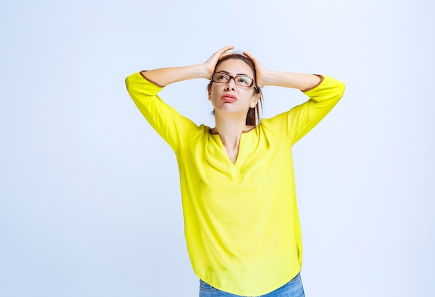 黄色いシャツを着た若い女性は思慮深く見えます