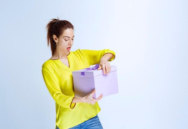 サプライズで紫のギフトボックスを開く黄色のシャツの若い女性