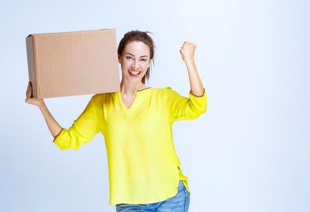 노란 셔츠를 입은 젊은 여성이 화물을 받고 즐거움 표시를 보여주고 있다