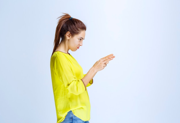 오른쪽에 뭔가를 보여주는 노란색 셔츠에 젊은 여자