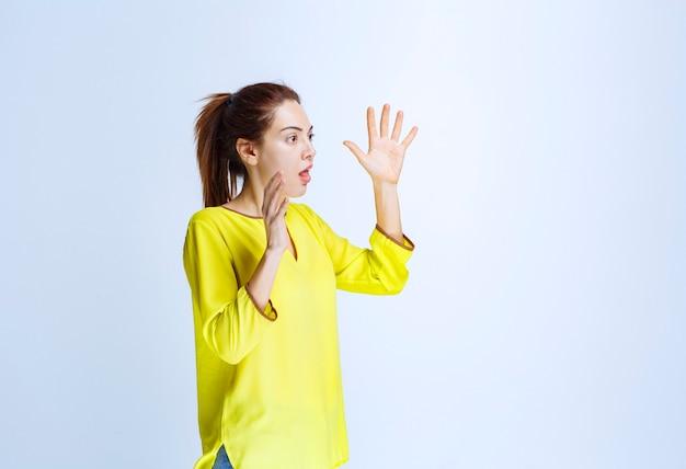 물건의 측정값을 보여주는 노란색 셔츠를 입은 젊은 여성