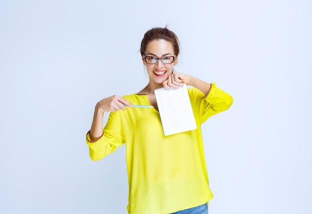 퀴즈 결과와 실수를 보여주는 노란색 셔츠를 입은 젊은 여성