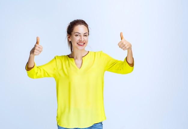 親指を立てて黄色いシャツを着た若い女性