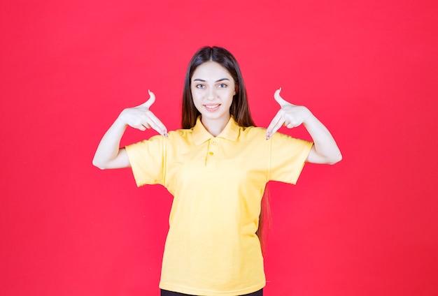 빨간 벽에 서서 자신을 가리키는 노란색 셔츠를 입은 젊은 여성