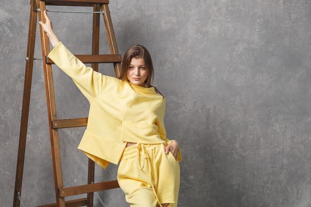 黄色のスポーツウェア、ズボン、スウェットシャツの若い女性。ファッショナブルなスポーツ服のコンセプト、屋内写真。スペースをコピーします。
