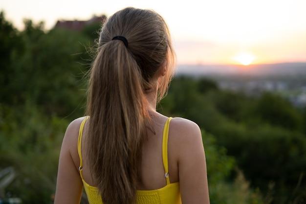 일몰 보기를 즐기는 녹색 초원에 서 있는 노란색 여름 드레스에 젊은 여자.