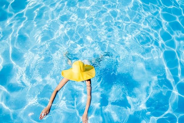 青い水と盆地で泳いで黄色い日よけ帽の若い女性。上からの概観