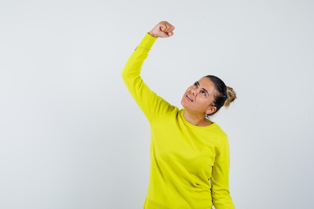 黄色いセーターと黒いズボンの若い女性は拳を握りしめ、幸せそうに見えます