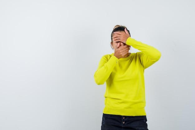 Молодая женщина в желтом свитере и черных брюках закрывает лицо руками и выглядит шокированной