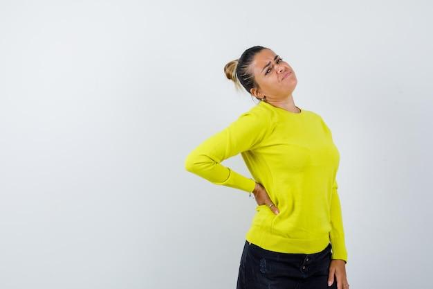 Молодая женщина в желтом свитере и черных штанах держит руку за талию и выглядит взволнованной