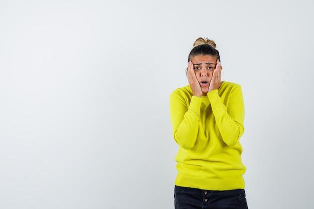 Молодая женщина в желтом свитере и черных штанах держится за щеки и выглядит взволнованной