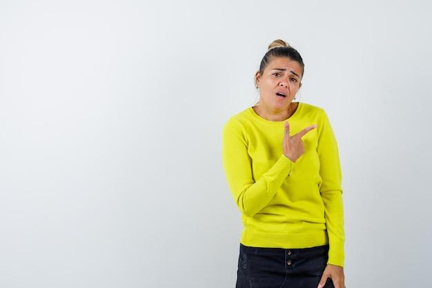 Молодая женщина в желтом свитере и черных штанах указывает вправо указательным пальцем, гримасничает и выглядит взволнованно