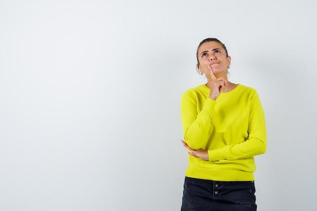 Молодая женщина в желтом свитере и черных брюках прикладывает указательный палец ко рту, думает о чем-то и выглядит задумчиво