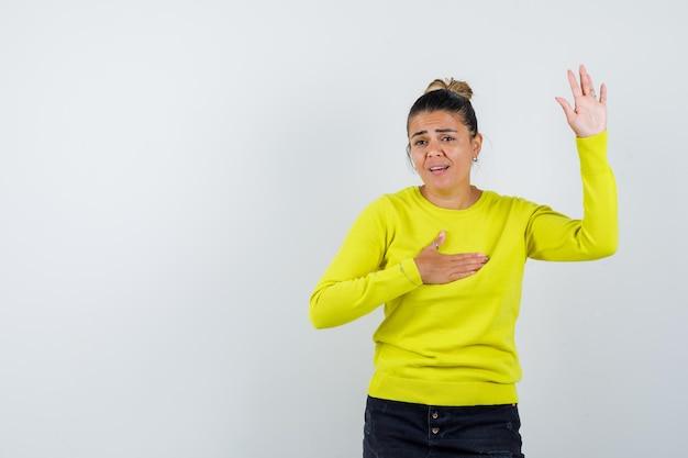 Молодая женщина в желтом свитере и черных штанах поднимает руку и держит руку на груди и выглядит взволнованной