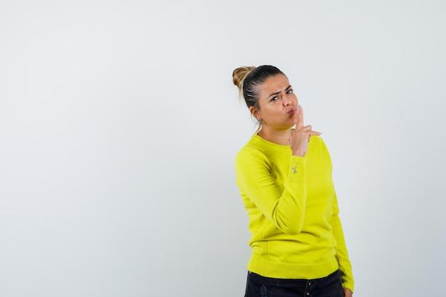 Молодая женщина в желтом свитере и черных брюках показывает жест пистолета и выглядит уверенно