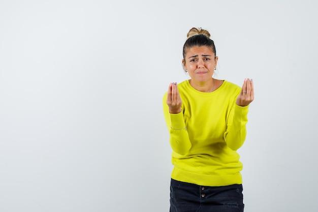 イタリアのジェスチャーを示し、感動したように見える黄色のセーターと黒のズボンの若い女性