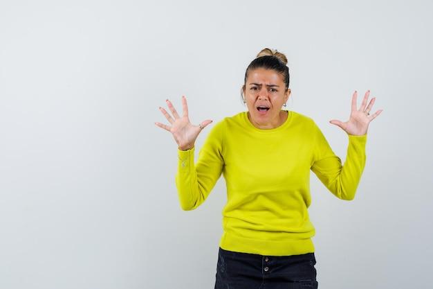 Молодая женщина в желтом свитере и черных брюках показывает знаки остановки и выглядит взволнованной