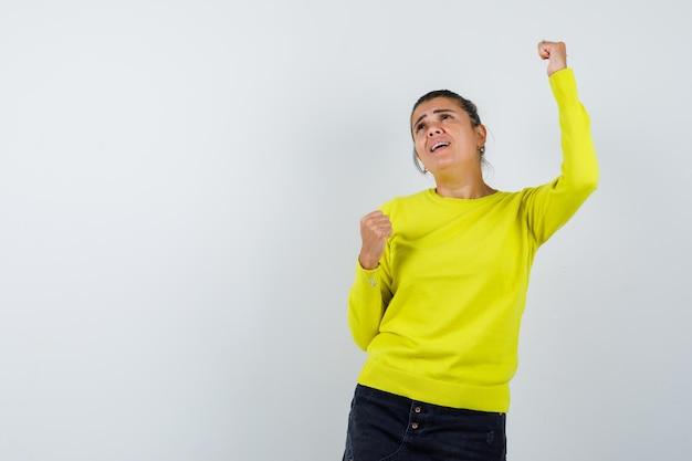 Молодая женщина в желтом свитере и черных брюках показывает жест победителя и выглядит счастливой