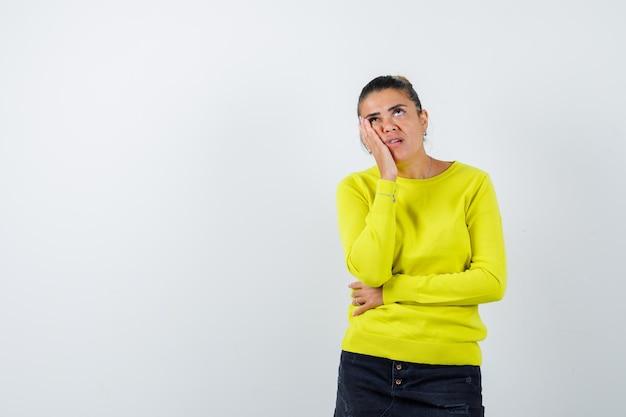 黄色いセーターと黒いズボンの若い女性がポーズを考えて物思いにふける