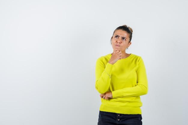 Молодая женщина в желтом свитере и черных штанах стоит в позе размышления и смотрит задумчиво