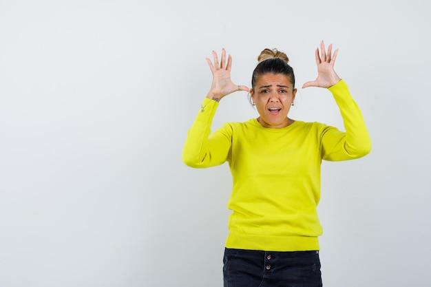 Молодая женщина в желтом свитере и черных штанах протягивает руки в позе капитуляции и выглядит взволнованной