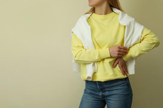 ベージュの表面に対して黄色のスウェットシャツの若い女性